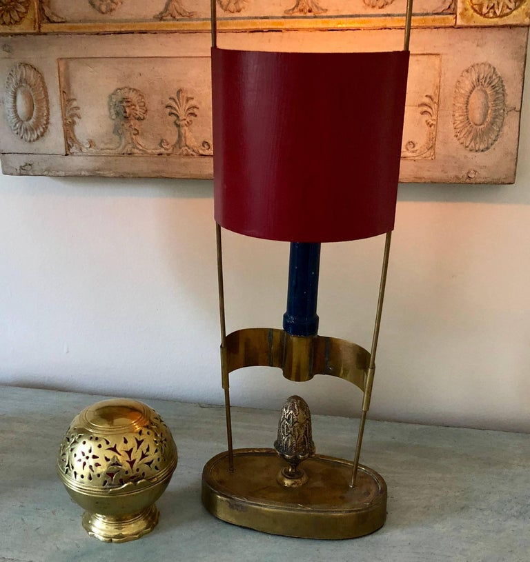 Small oval brass candlestick with a red painted shade and acorn centerpiece, Sweden early 19th Century.