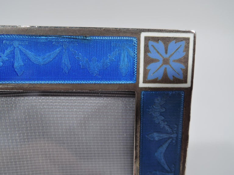 Edwardian Regency silver and enamel picture frame, ca 1910. Rectangular window with flat surround. Bow-tied floral garland on blue lined ground. Corner squares have white borders and are inset with violet paterae. With glass, silk lining, and velvet