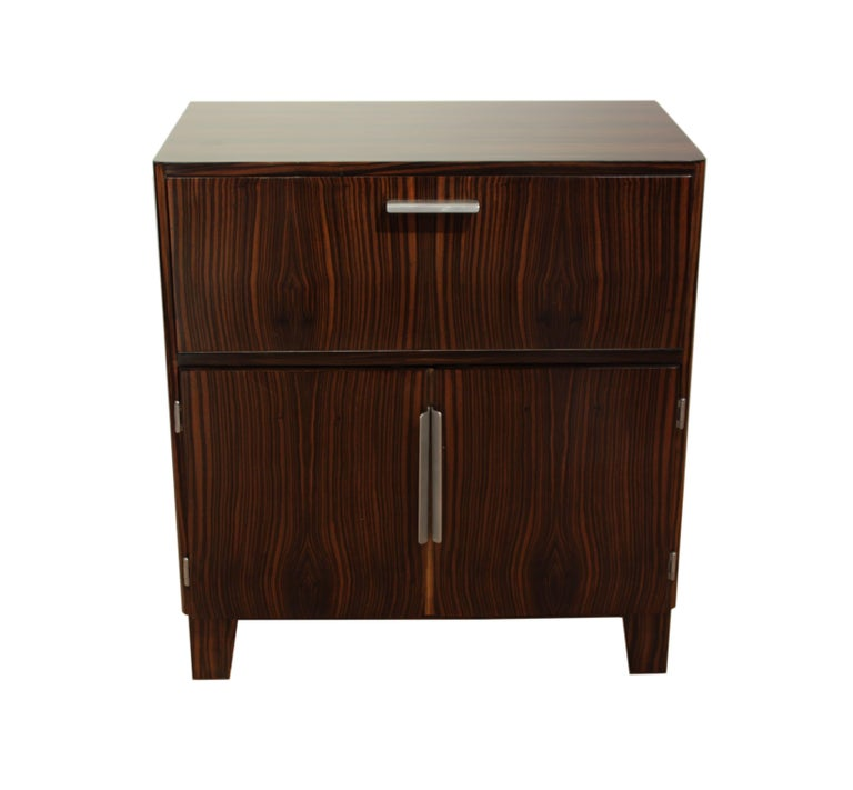 Wonderful small Art Deco bar furniture / drinks cabinet from France, circa 1930s.  Nice Macassar ebony veneer, lacquered with clear piano lacquer and high-gloss polished.   On the top, it has one fold-out bar compartment with magnets and chains.