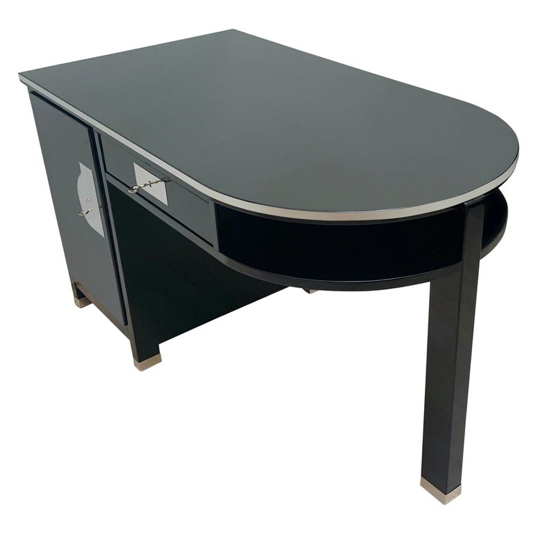 Very elegant, small and functional Art Decowriting desk from France, circa 1930.  Black piano lacquer on hardwood veneered on softwood. High-gloss polished decorative metal strips around the plate and all five legs. Nickel-plated handle on the