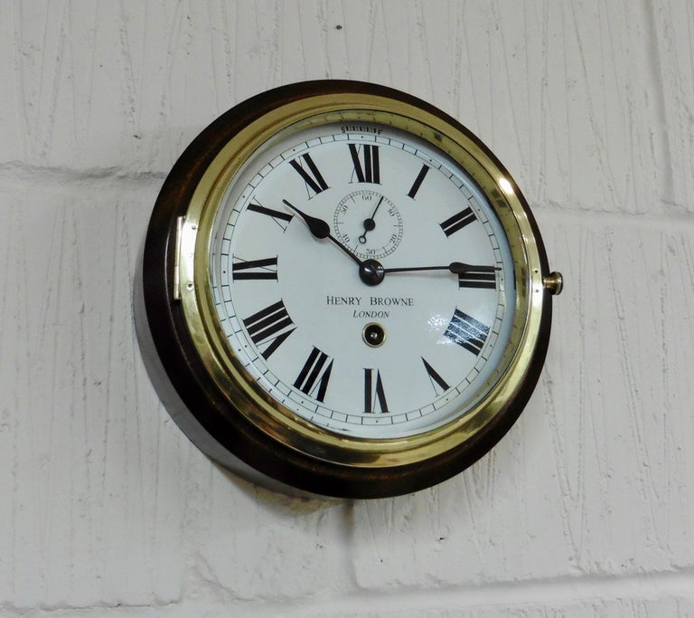 Small brass ships clock with a heavy cast brass bezel mounted in a mahogany surround.   Enamel dial with Roman numerals, 'blued' steel hands signed 'Henry Browne, London.  Eight day spring driven movement with platform escapement, circa
