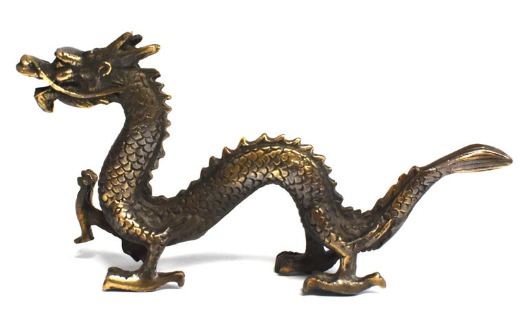 A beautiful small statue of dragon in the late Qing dynasty style. The four-clawed dragon has one front talon in pursuit of its subject, likely a flaming pearl, while the other three are firmly planted on the ground. The head strains forward with