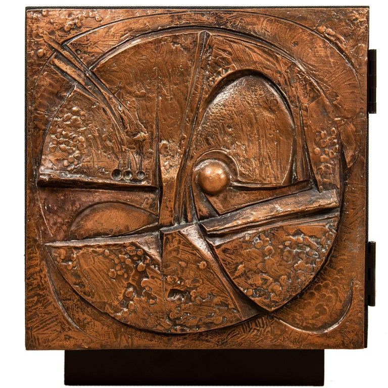 This unusual one of kind artist piece in the Brutalist style is hand cast from a mold and made from a hard epoxy composite. The vintage door front has been mounted to 3/4