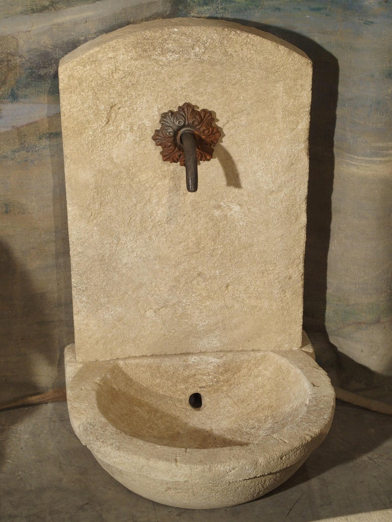 This small limestone fountain from France has a circular basin with hole for drainage. The basin extends out from a vertical back support, and on top of this, is a carved upper portion with sloped shoulders. A rusted spout is surrounded by a rusted