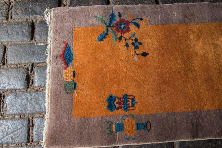 Small Chinese Art Deco rug with a taupe border, yellow-gold field, and multi-color decorative features.