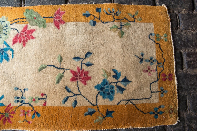 Small Chinese Art Deco wool rug with a deep yellow-gold border, beige field with multi-color decorative features.