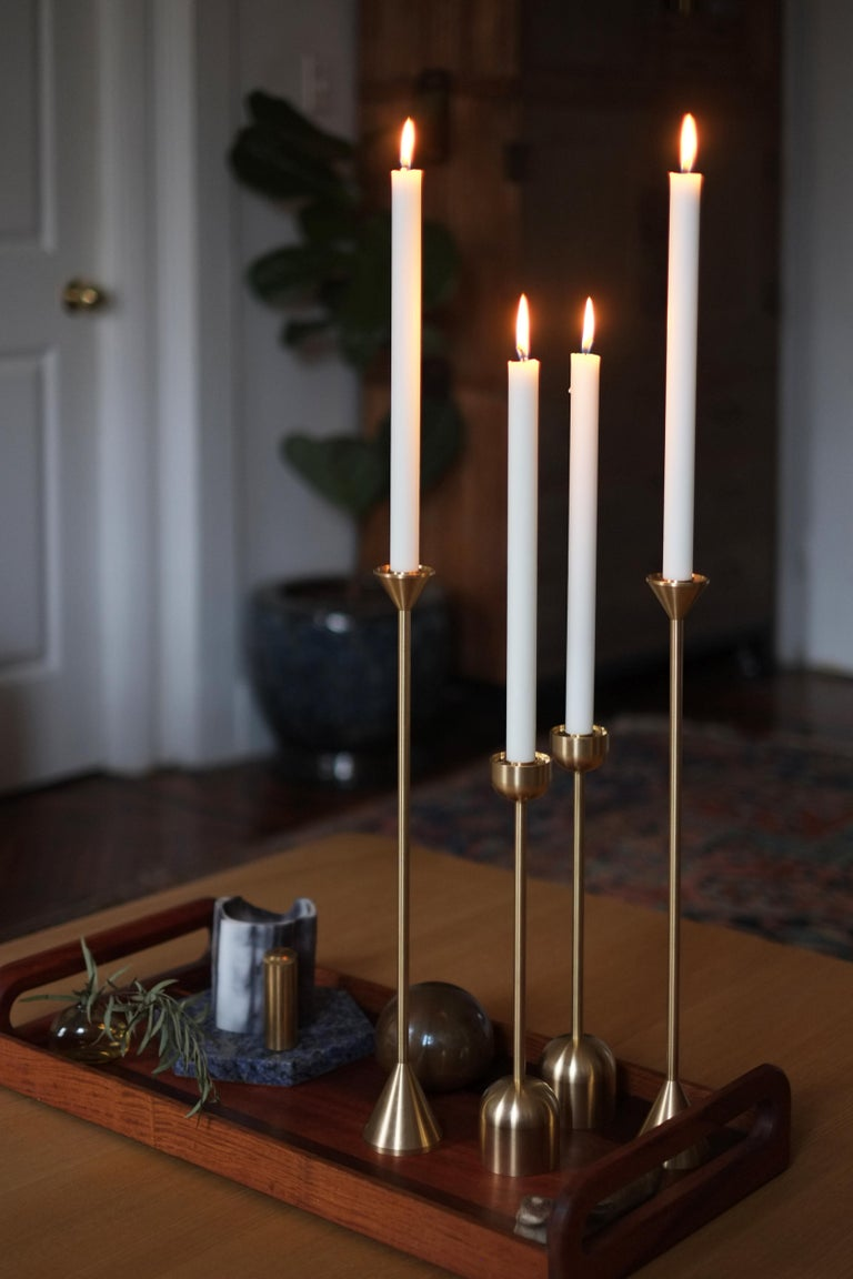 The tall, simple design of this brass candle holder adds a modern twist to a classic object and creates an elegant accent in any living or dining room.