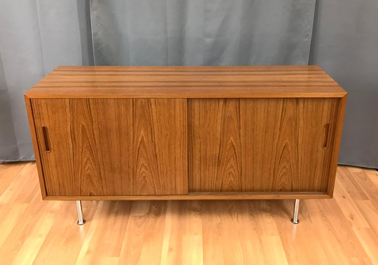 Small credenza or sideboard in Teak by Paul Hundevad, circa 1960s. Has two sliding front doors, behind them on the right are two adjustable shelves, and on your left one adjustable shelf with a small drawer above. Inside are Beech, the unit sits on