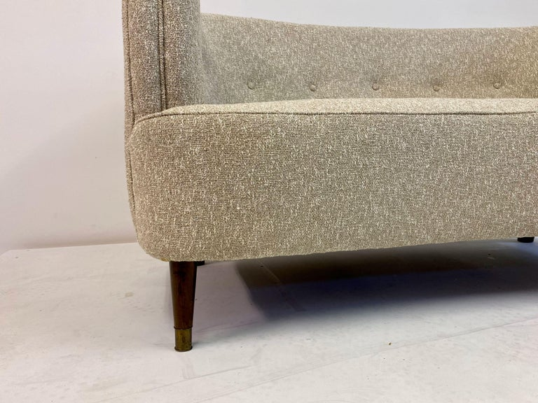 Two-seat sofa  Newly upholstered in Lelièvre Granito Nacre fabric  Tub shaped  Stained beech legs  Brass feet  Danish 1940s.