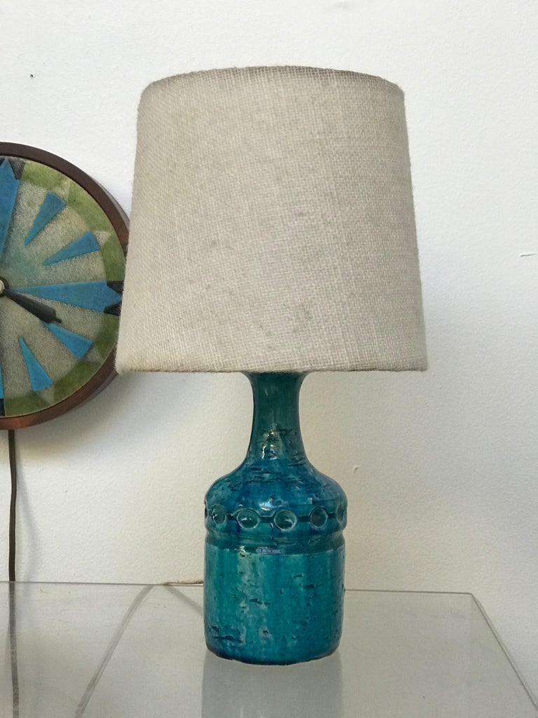 Diminutive early ceramic Danish table lamp by Bent Nordsted for Lyksaer Belysning. Original linen shade - light wear. Very nice vintage condition. Wiring works fine - it has not been replaced. Measures: 13