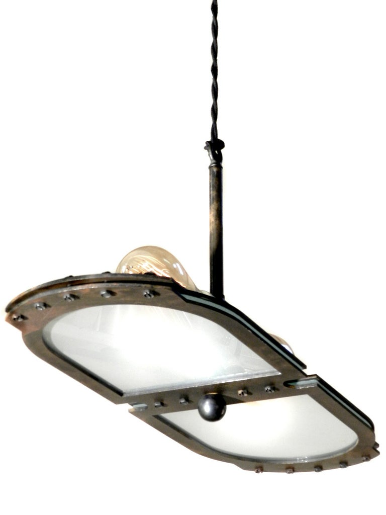 This small tracery style Industrial pendant fits comfortably with most styles. It's very architectural with clean lines… just look at the profile. The heavy steel frame has an aged patina and Industrial accents that are not over done. We designed