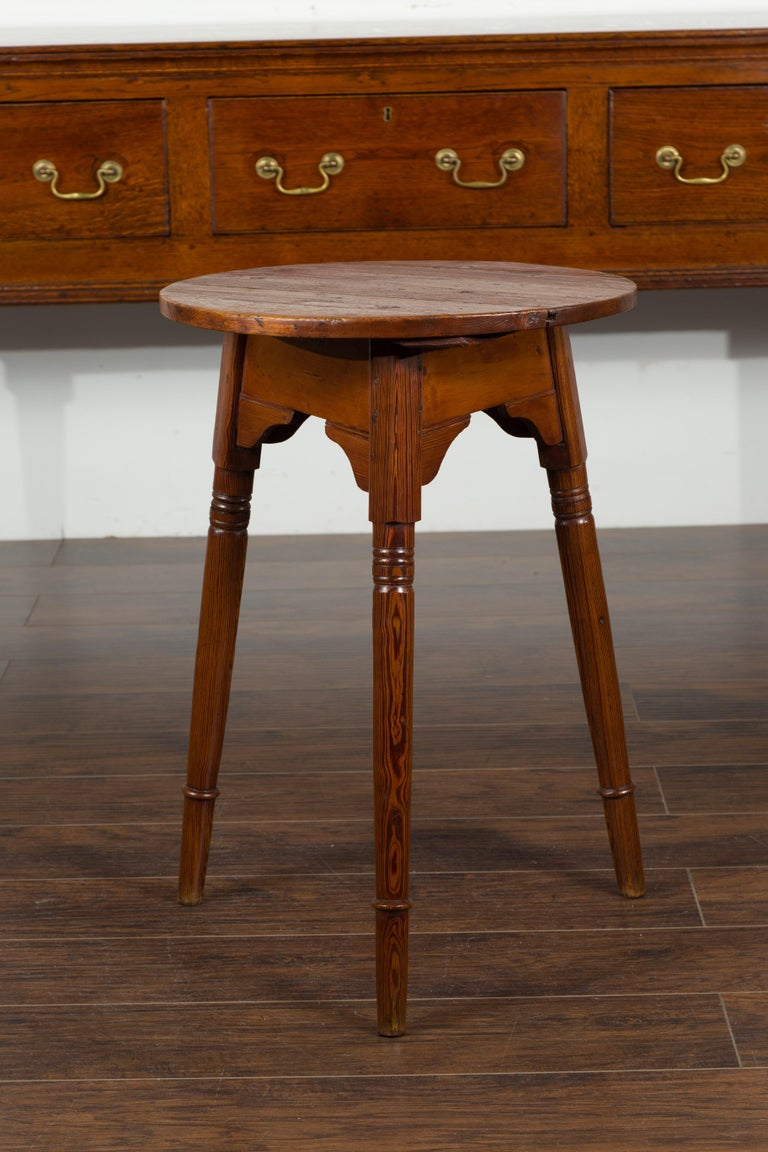 A small English pine cricket table from the mid-19th century, with carved apron and slender turned legs. Born in England during the second quarter of the 19th century, this pine cricket table features a circular top sitting above an apron carved on