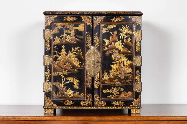 An English black and gold chinoiserie small cabinet from the late 19th century, with 10 inner drawers. Born in England during the last decade of the 19th century, this small cabinet features a black lacquered silhouette, adorned with a golden