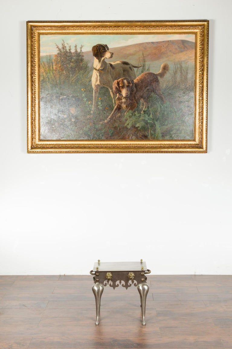 An English steel and brass small table from the early 20th century, with lion head ring pulls, cut-out apron and curving legs. Created in England during the early years of the 20th century, this steel table features a rectangular top accented with