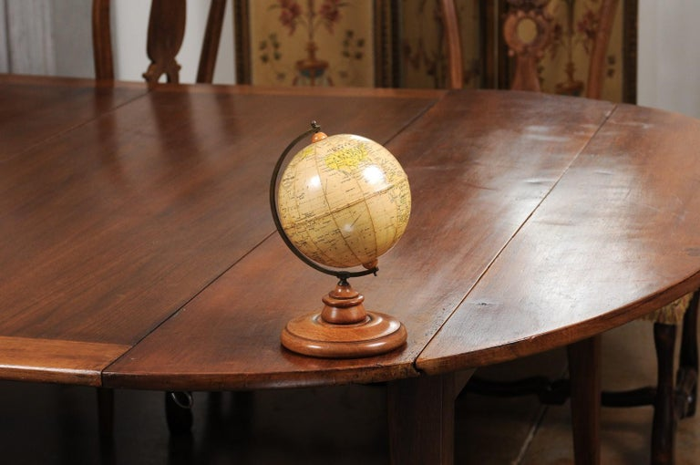 A small English terrestrial globe from the 20th century, with brass protractor and circular wooden base. Created in England during the 20th century by George Philip & Son in London, this terrestrial globe is connected through a brass protractor to a