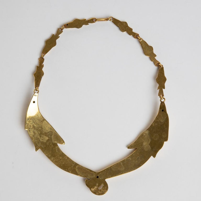 Gilded bronze necklace made up of two semi-rigid parts surrounding the neck.  The front part is made up of two large fish holding each other by the tail, in the centre of the necklace.  Each fish holds in its mouth a succession of six small fish