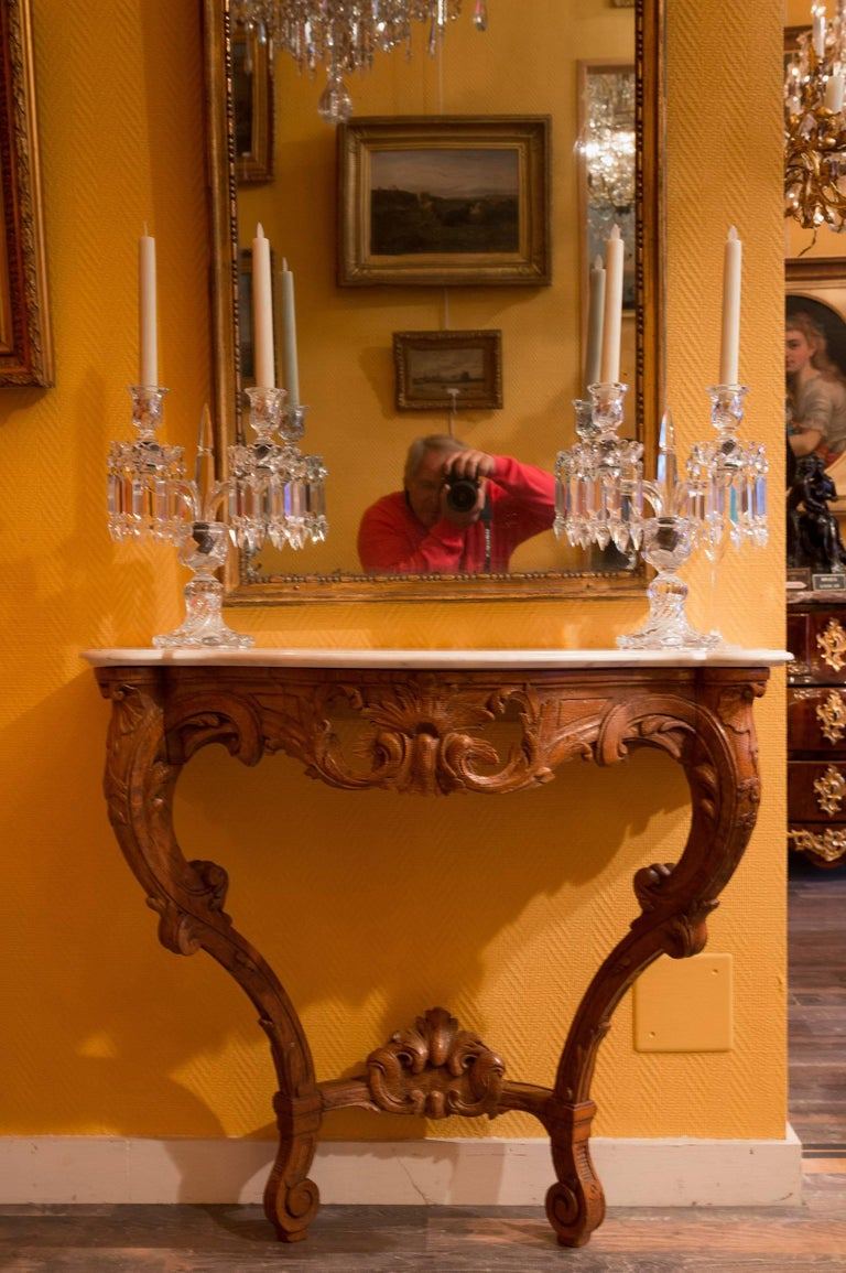 A lovely and very decorative Louis XV Rococo style console table in solid fruitwood, on two elaborately carved front supports, the base with an upturned cross stretcher supporting an elaborately carved flower, well-carved leaf and scroll decoration