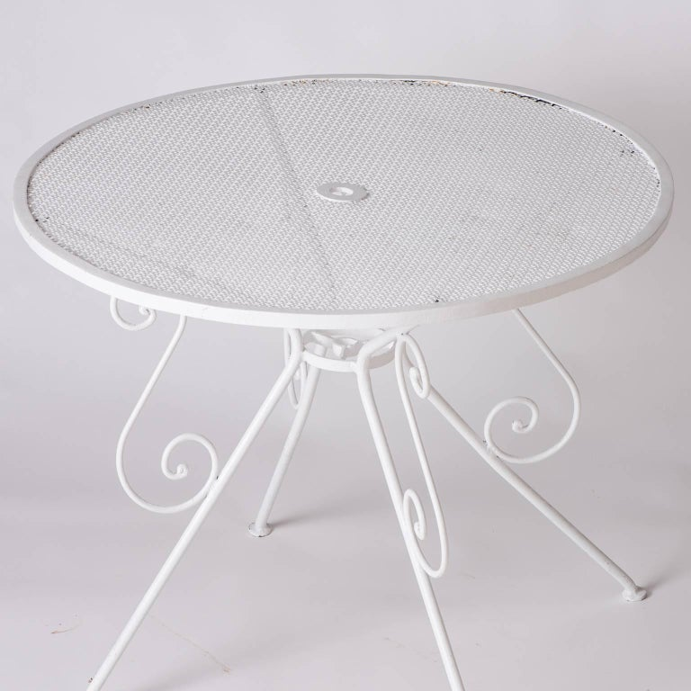 A French wrought iron garden table with a pierced top and an umbrella hole in the center, circa 1950. It is in great condition and has been recently painted with weather resistant paint.