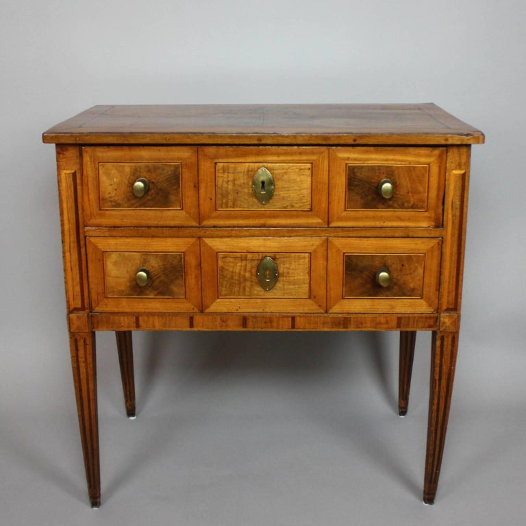 A small German Neoclassical marquetry commode with a rectangular top above two drawers each with three walnut panels and fine banding. With corresponding marquetry on sides and top, on square tapering legs. With brass mounts and a beautifully