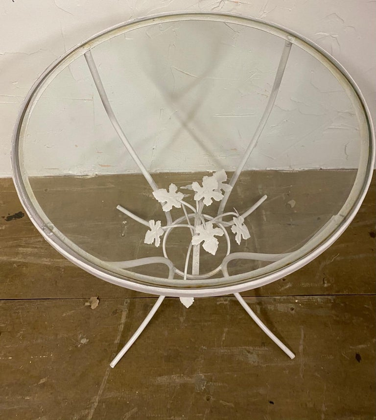 Petite round metal and glass painted Salterini style garden side table with center leaf design.
