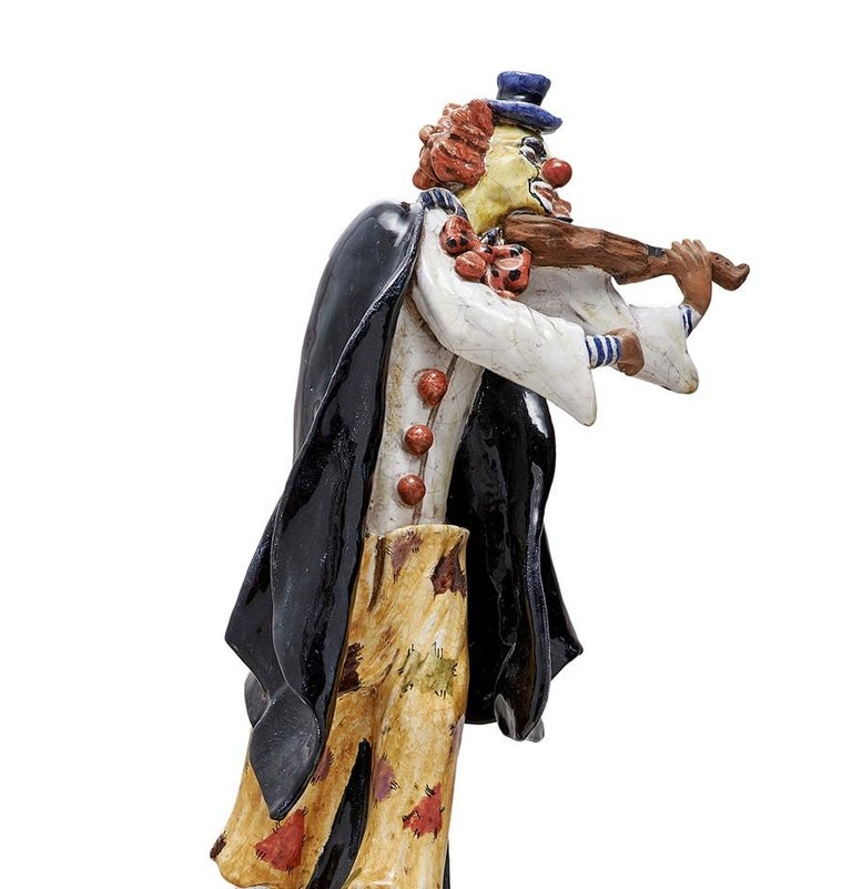 This whimsical statuette features Grock, a Swiss clown, composer and musician from the 20th century known as the