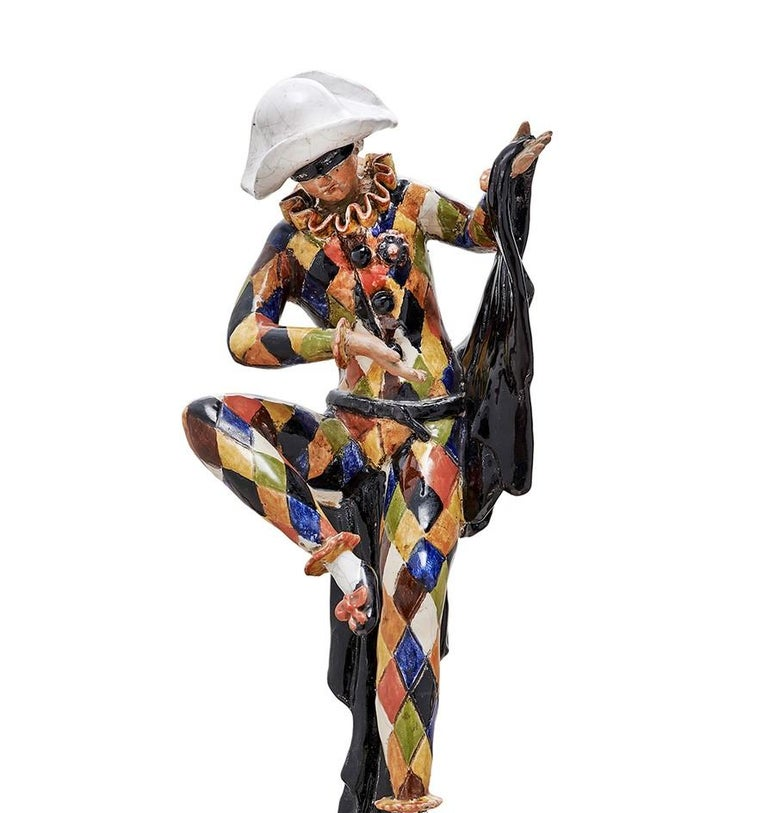 Mysterious yet alluring, this exquisite statue strikes a poetic balance between art and decor. One of the most recognizable characters from the Commedia dell'Arte, the Harlequin is here depicted performing a magic trick with his swooping black cape.