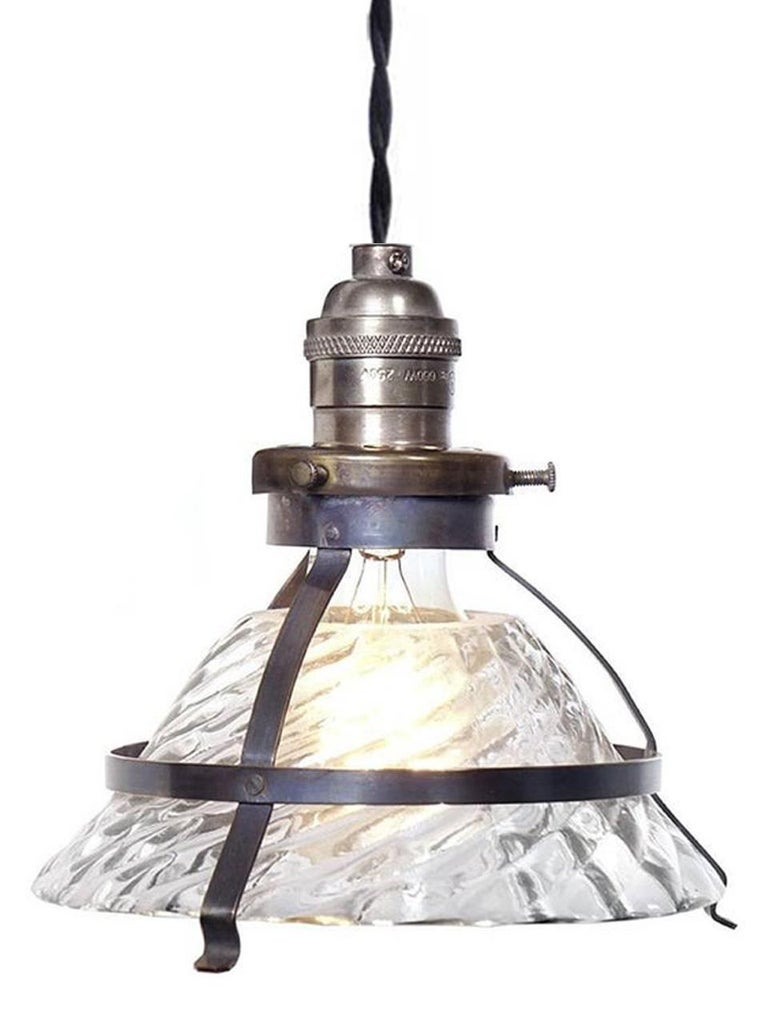 This is a unique industrial snap-in shade fixture. This shade was in the style of an early X-Ray lamp reflector. They have an elegant and complex industrial look with a 6.6 inch diameter and standard size brass socket. The combination of a clear