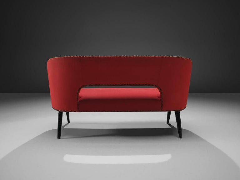 Settee, red fabric, wood, Italy, circa 1960.  This elegant Italian sofa has been upholstered in red fabric and has tall tapered legs. The two-seat settee has a transparent and open character. Due to the bent back and the thick seat the sofa sits