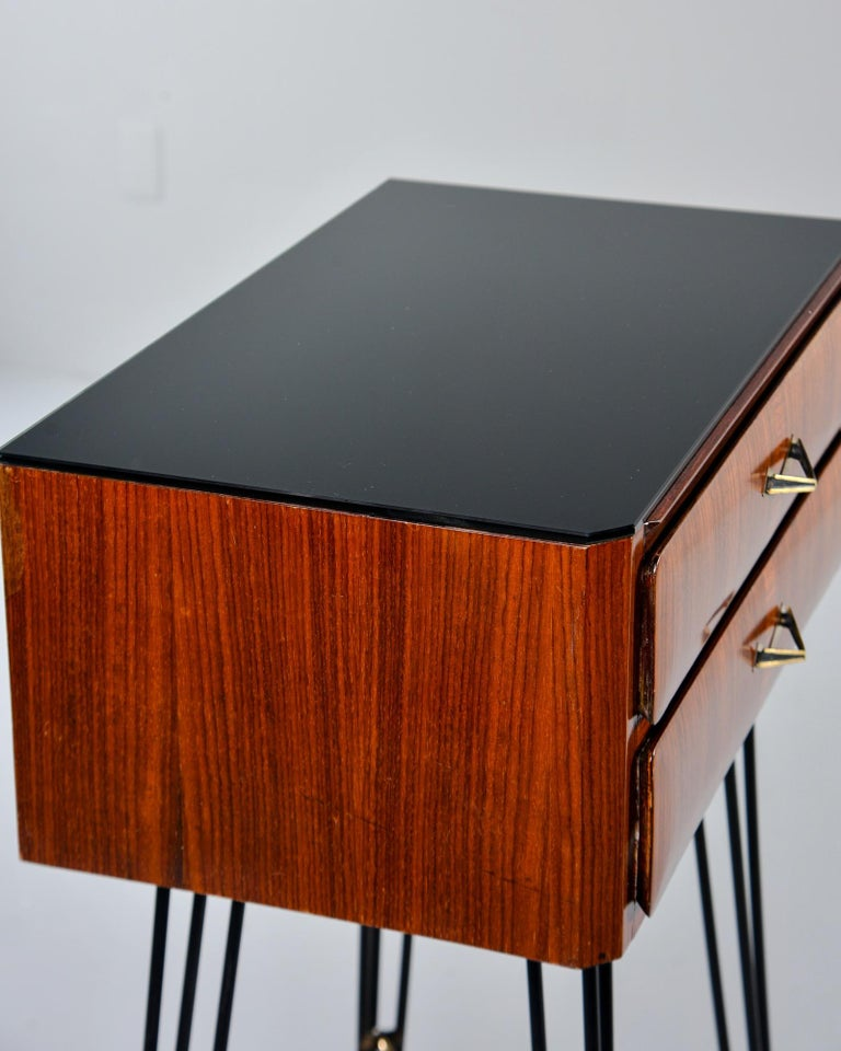 Italian side cabinet features slender black iron hairpin legs with brass capped feet, brass X-form stretchers and two-drawer cabinet in nicely figured wood veneer, circa late 1950s. Drawers have dovetail construction, original triangle form pulls