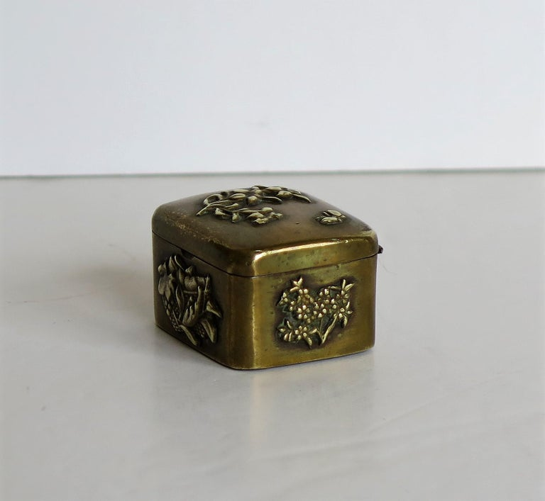 This is a small Japanese bronze and brass box with a hinged lid and different detailed embossed applied patterns of flowers and leaves, dating to the 19th century Meiji period.  The box has a rectangular shape with a hinged slightly domed top