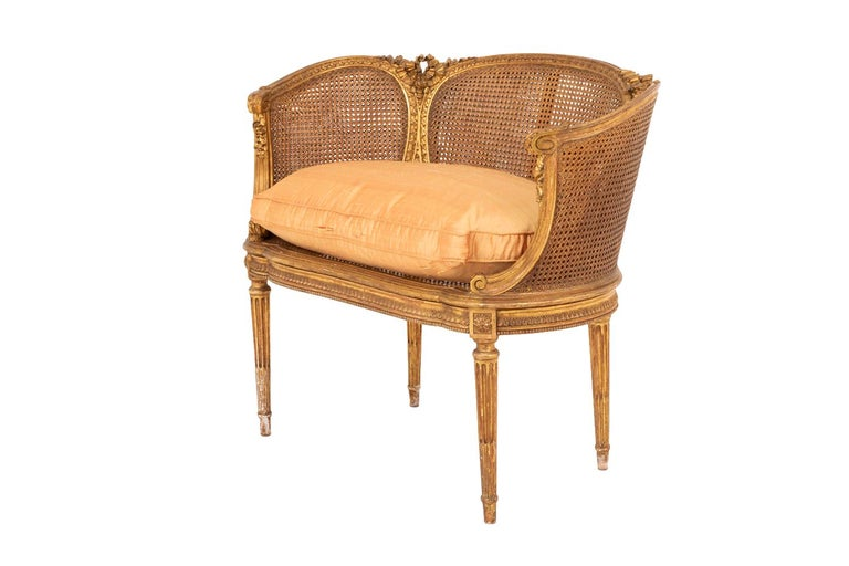 Small Louis XVI style cane sofa in giltwood standing on four tapered fluted and chandelles legs topped by joints adorned with rosettes. Scalloped apron in profile, decorated with a water leaves frieze and a beads frieze. Arm supports on the leg line
