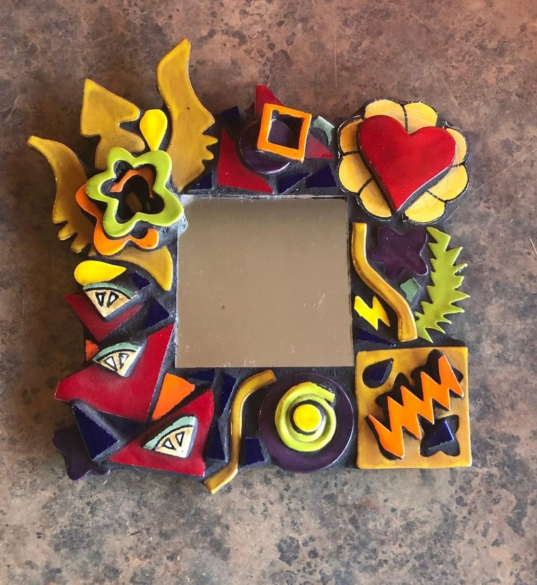Very cool Memphis style small wall mirror signed Hill Brin, circa 1990s. There is a lot of intricate pottery detail and image overlap on the frame of the handmade mirror.