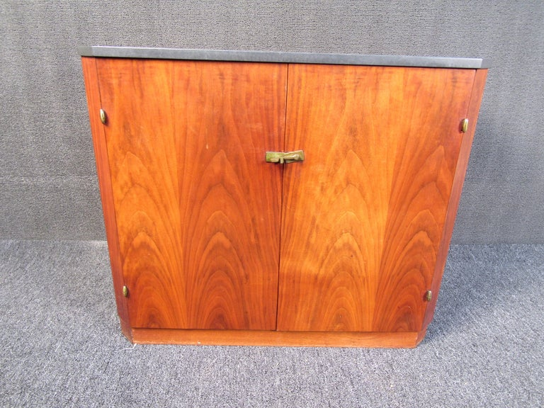 This simple midcentury cabinet features a heavy slate top and a beautiful walnut base and bottom. Able to be stacked on an existing piece, or used as a freestanding cabinet this piece will add versatile functionality to any home. Please confirm the