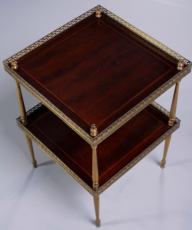 Two-tier brass and mahogany side table features decorative finials, brass galleries and tapered legs. Unknown maker. Found in England, circa 1960s.