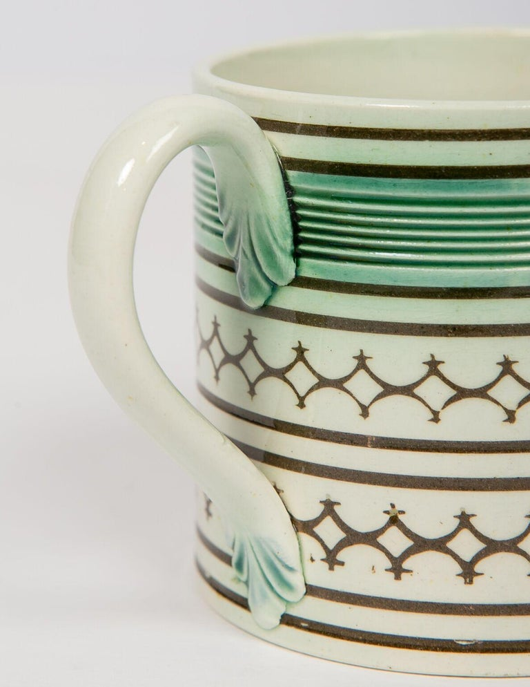 Small Mochaware mug England, circa 1820 Decorated with rouletted and green glaze decoration above two rows of engine-turned black diamonds. Dimensions: Diameter 2.5