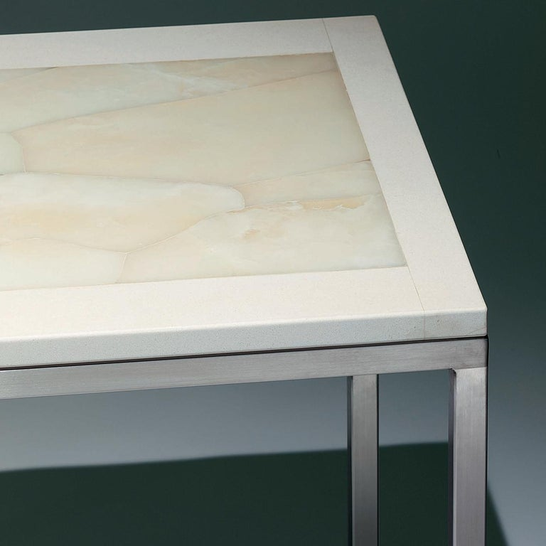This side table features a hand inlaid white onyx top trimmed in ivory-colored limestone. Its matte, smooth surface provides a serene, calm look. Polished stainless steel legs complete the item with an added touch of sheen. This clean-styled,