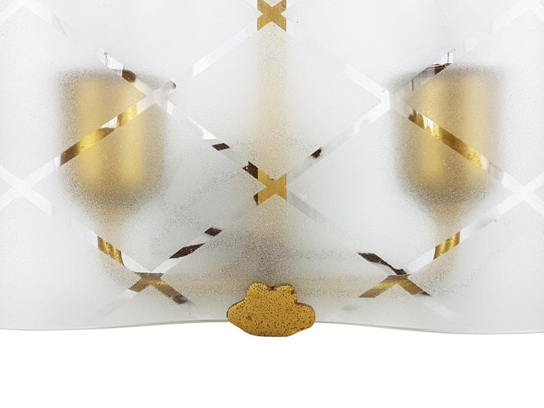 This pair of small wall lamps was produced in Italy, circa 1940s in the manner of Pietro Chiesa. It is made from a brass structure with a sandblasted and bent glass shade. Very good vintage condition: the sconces have never been used (they come from