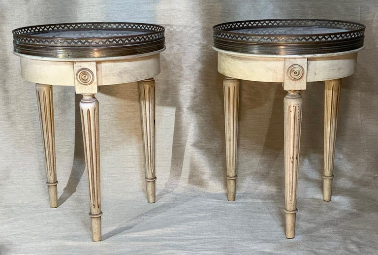 Elegant pair of vintage side tables made of three legs carved wood, white -gray marble top surrounded with decorative Brass trimming.
