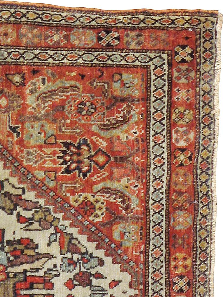 An antique Persian Fereghan rug from the late 19th century. A giant stepped ivory diamond medallion encloses a detailed complex palmette and encircling floral wreath and is set on a rust Herati field. An X-in-octagon main border and two ivory minors
