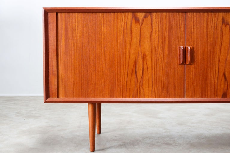 Rare small Danish design sideboard / credenza by Svend Aage Madsen for the Faarup Mobelfabrik in the 1950s. The sideboard has a amazing clean design and small size. The tambour doors disappear completely when opened and the craftsmanship on this