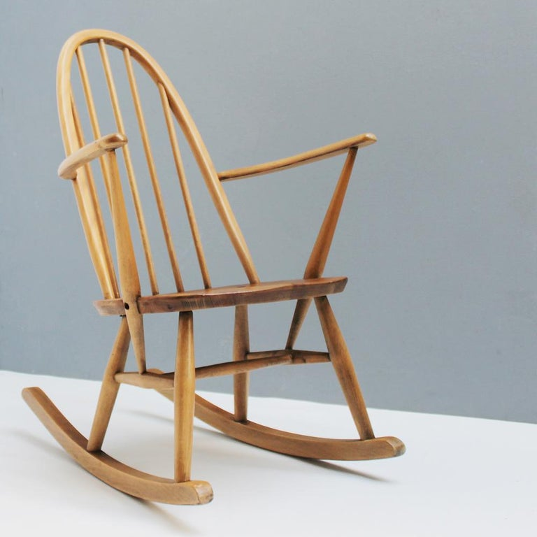Charming small rocking chair. Quaker model 428 by Lucian Ercolani for Ercol, England. This rocking chair is based on the Ercol Quaker chair, a stylish development of the infamous Windsor chair. It features a solid elm seat and solid beech