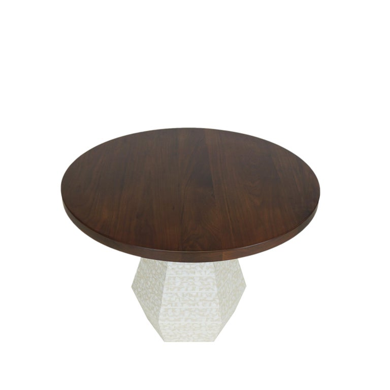 """Our Capriz dining table is a modern round table with a walnut top finished in a satin lacquer. The hexagon shaped based is covered in Capiz shells, often referred to as """"glass oysters"""" because of their translucent appearance. Custom sizes available."""