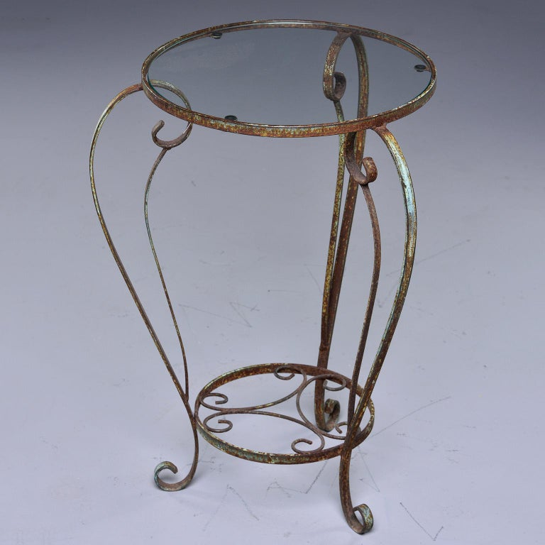 Found in France, this circa 1930s side table has a curvy iron frame with a green painted finish and clear, round glass top. This table can be used indoors or out. Unknown maker.