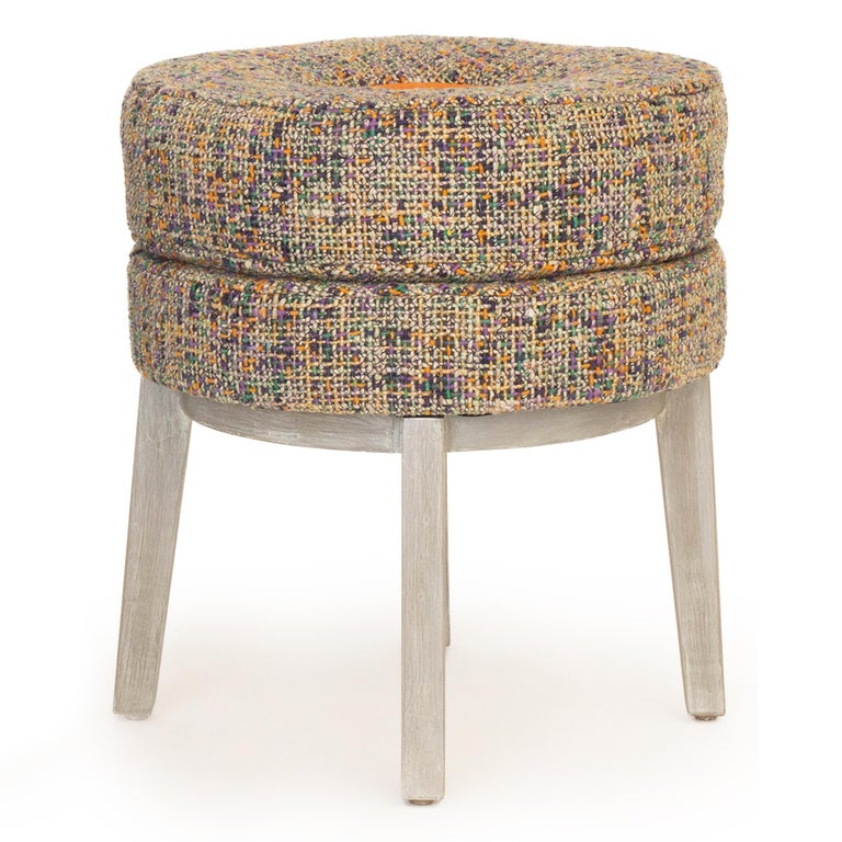 This small round stool is upholstered in a colorful tweed fabric with an orange vinyl interior accent. Made with poplar wood painted with a Swedish finish. Sturdy base with a comfortable foam cushion seat, it is great for all ages. Check for current