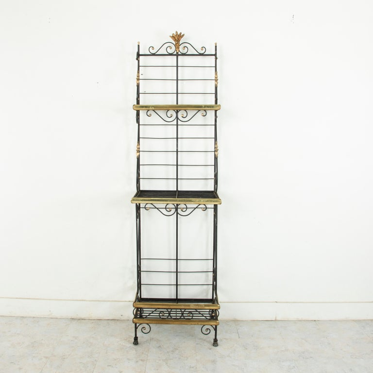 A rare find in a unique small scale, this mid-20th century French iron baker's rack is trimmed in brass around each of its three shelves. The shelves are joined by scrolling iron detailed with brass turnings that lend support as well as an aesthetic