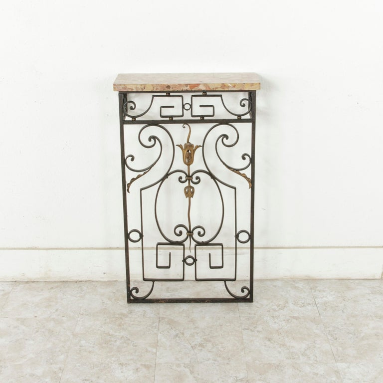 This small scale French iron console table from the early 20th century features a mix of intricate scrolling and geometric angles detailed with gold spheres and a leaf motif. Crowned with a marble top, this piece would be ideal in a small entryway