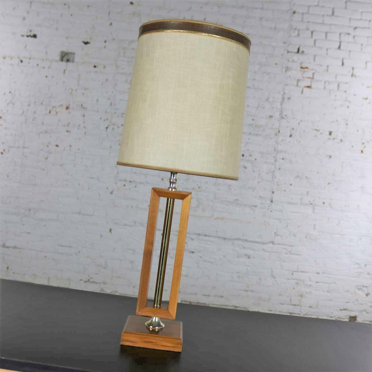 Handsome small-scale Mid-Century Modern lamp in walnut with brass detail in the style of Laurel Lamp Mfg. Co. It is in wonderful condition having been rewired and given a new socket. The walnut and brass are beautiful, and it retains its original