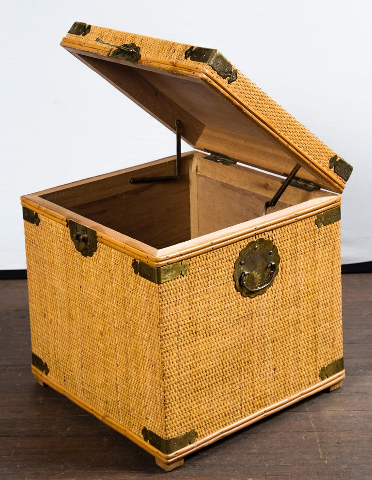 Small square rattan trunk with decorative brass trim and hardware.