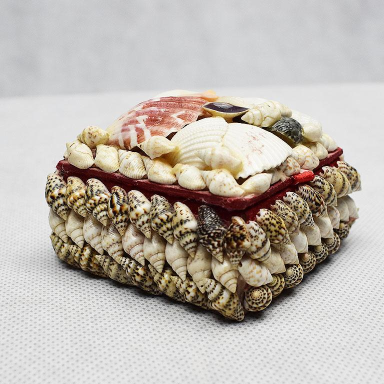 Small square shell encrusted trinket box. Covered in a variety of shells, this box opens to reveal a red-lined fabric interior. This would be the perfect piece to display on a coffee table or vanity to hide jewelry or other trinkets or jewelry.