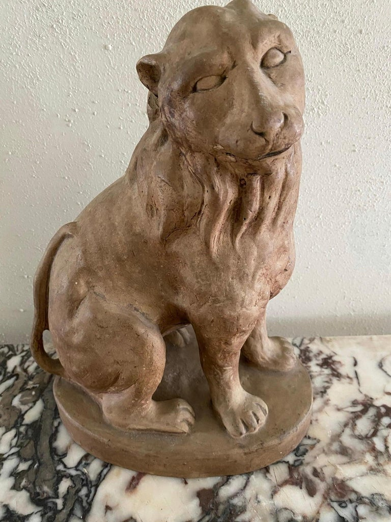 Clay figure of a seated lion with a sweet countenance.